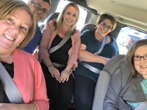People smiling while sharing a car ride.